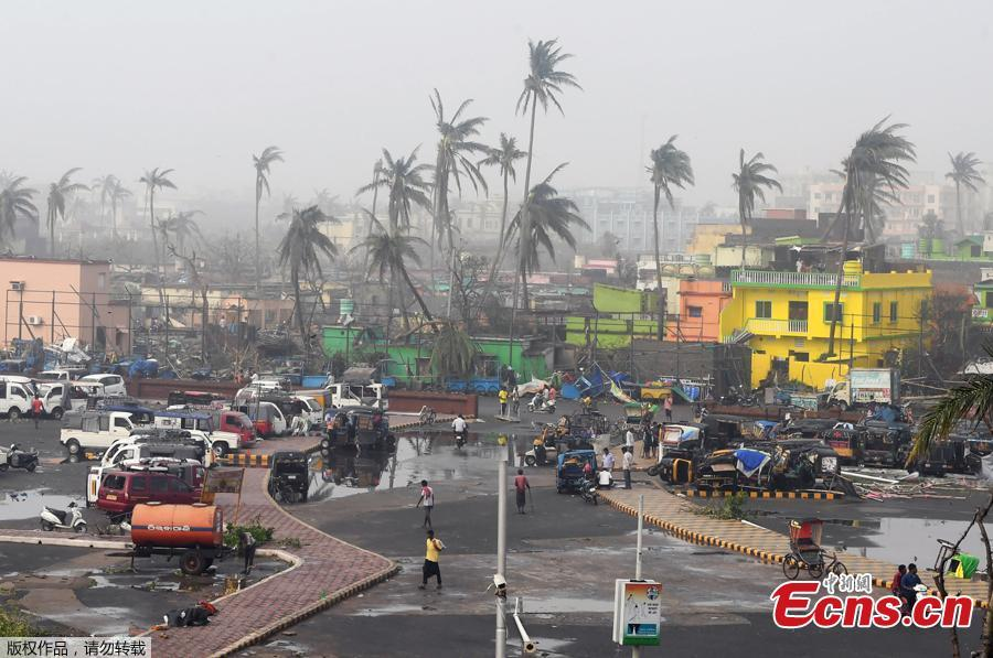 People gather next to storm-damaged buildings and palm trees in Puri in the eastern Indian state of Odisha on May 4, 2019, after Cyclone Fani swept through the area.  Cyclone Fani, one of the biggest to hit India in years, barrelled into Bangladesh on May 4 after leaving a trail of deadly destruction in India. (Photo/Agencies)