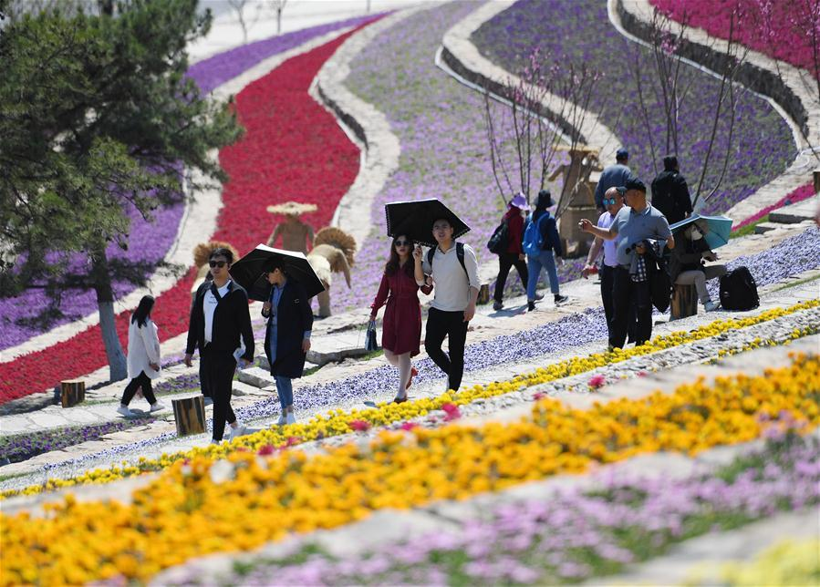Tourists visit Beijing International Horticultural Exhibition in Yanqing District of Beijing, capital of China, on May 1, 2019. Beijing International Horticultural Exhibition welcomed its first tourist peak by serving more than 320,000 tourists during the four-day May Day holiday, the organizer said Saturday. Some 132 activities, including float parades, world ethnic and folk cultural performances, and culture and art carnivals staged by central and eastern European countries, were held during the holiday. With the theme of \