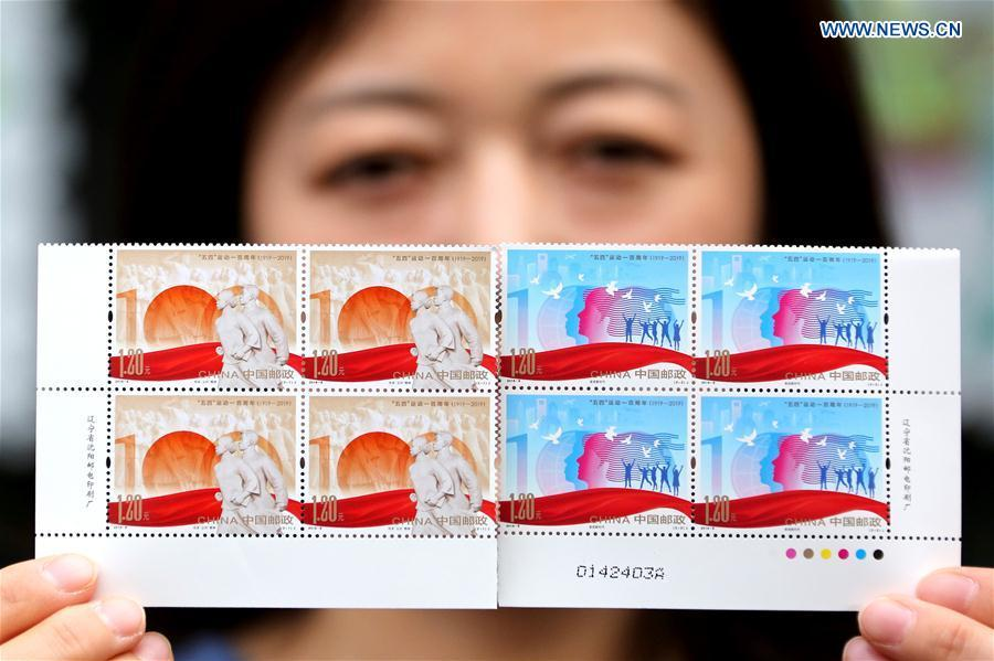 A stuff member of the Zaozhuang branch office of China Post shows the commemorative stamps for the 100 anniversary of the May 4th Movement, in Zaozhuang City, east China\'s Shandong Province, May 4, 2019. China Post on Saturday issued a set of two commemorative stamps marking the 100 anniversary of the May Fourth Movement. (Xinhua/Sun Zhongzhe)
