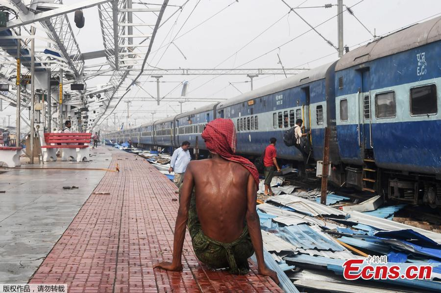 An Indian man sits on the train station platform as people look through debris on the tracks at the damaged railway station in Puri in the eastern Indian state of Odisha on May 4, 2019, after Cyclone Fani swept through the area.  Cyclone Fani, one of the biggest to hit India in years, barreled into Bangladesh on May 4 after leaving a trail of deadly destruction in India.  (Photo/Agencies)