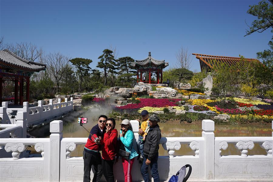 Visitors take selfies at the Beijing Garden at the International Horticultural Exhibition 2019 Beijing in Yanqing District of Beijing, capital of China, May 1, 2019. Beijing International Horticultural Exhibition welcomed its first tourist peak by serving more than 320,000 tourists during the four-day May Day holiday, the organizer said Saturday. Some 132 activities, including float parades, world ethnic and folk cultural performances, and culture and art carnivals staged by central and eastern European countries, were held during the holiday. With the theme of \
