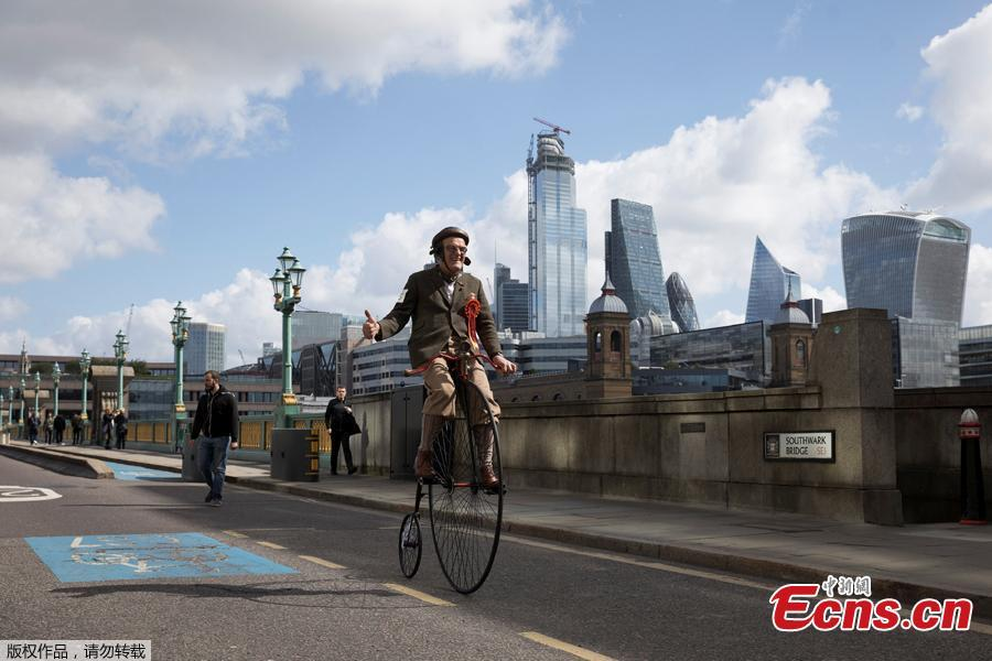 A participant rides his Penny-Farthing across Southwark Bridge as he takes part in the annual Tweed Run across London, Britain May 4, 2019. They ride through London\'s historic streets, stopping mid way for a picnic and ending with a traditional British \