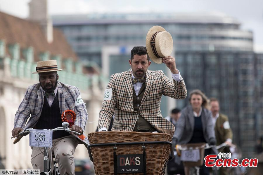 A participant gestures with his hat as he rides across Westminster Bridge during the annual Tweed Run across London, Britain May 4, 2019. (Photo/Agencies)