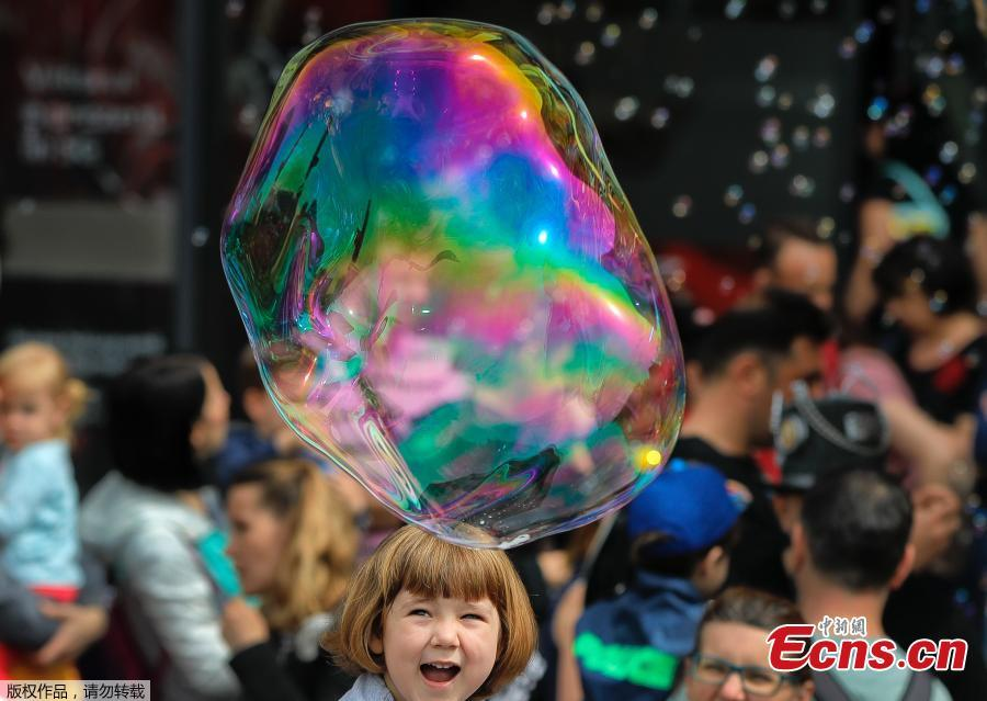 A child laughs at a soap bubble during the Global Bubble Parade in Bucharest, Romania, Sunday, May 5, 2019. Dozens took part in the Global Bubble Parade, an international event, held in 125 cities across 60 countries, according to the organizers, that brings together soap bubble fans. (Photo/Agencies)