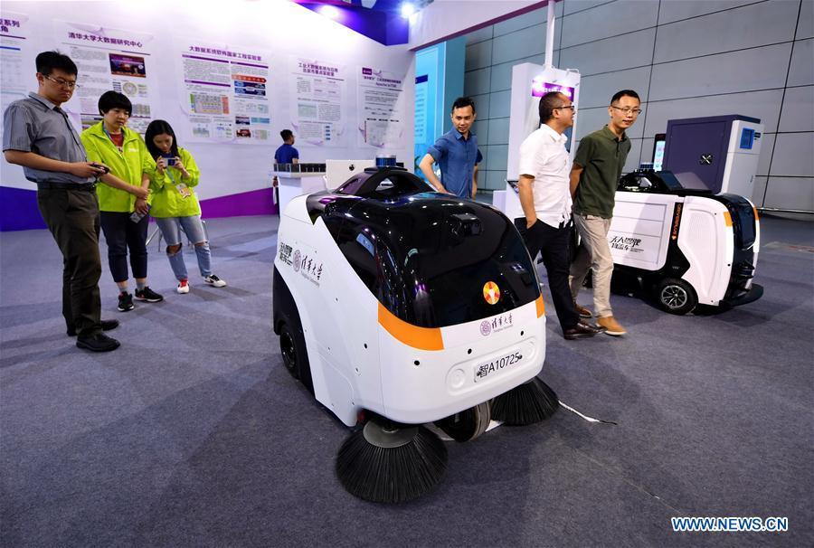 Visitors look at an auto-pilot cleaning vehicle (L) and an auto-pilot logistics vehicle at the 2nd Digital China Exhibition in Fuzhou, southeast China\'s Fujian Province, May 5, 2019. The 2nd Digital China Exhibition runs from May 5 to 9 at the Fuzhou Strait International Conference & Exhibition Center. (Xinhua/Lin Shanchuan)