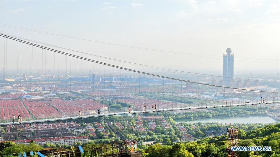 Aerial photo taken on May 4, 2019 shows tourists walking on a glass bridge at the Huaxi World Adventure Park in Huaxi Village of Jiangyin City, east China\'s Jiangsu Province. The 518-meter-long glass bridge hangs more than 100 meters above ground level at the park. It is made of panes of 35-mm-thick glass. Each glass can hold a maximum weight of 4.7 tonnes. Around 2,600 people can cross the bridge at a time. (Xinhua/Xu Congjun)