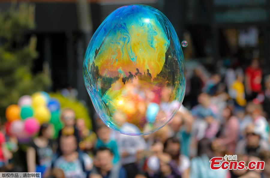 Participants in the Global Bubble Parade are reflected in a soap balloon in Bucharest, Romania, Sunday, May 5, 2019. Dozens took part in the Global Bubble Parade, an international event, held in 125 cities across 60 countries, according to the organizers, that brings together soap bubble fans.
