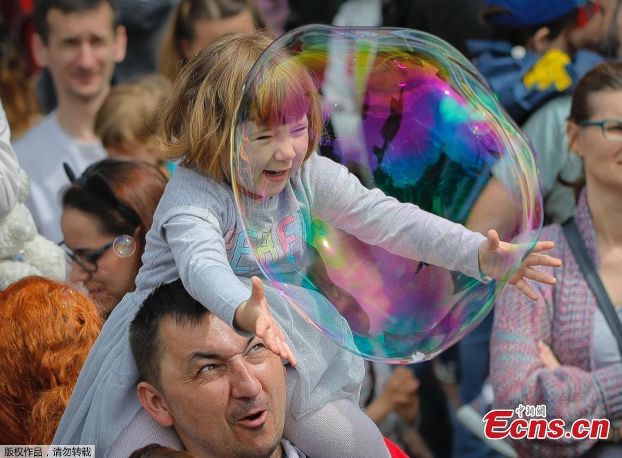 A child reaches for a soap bubble during the Global Bubble Parade in Bucharest, Romania, Sunday, May 5, 2019. Dozens took part in the Global Bubble Parade, an international event, held in 125 cities across 60 countries, according to the organizers, that brings together soap bubble fans.  (Photo/Agencies)