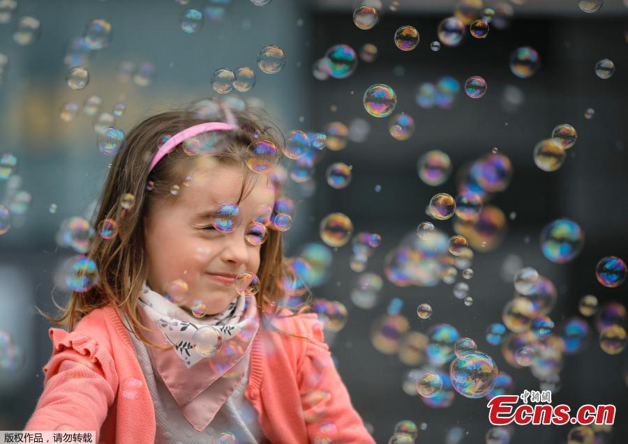 Soap bubbles land on a girl\'s face during the Global Bubble Parade in Bucharest, Romania, Sunday, May 5, 2019. Dozens took part in the Global Bubble Parade, an international event, held in 125 cities across 60 countries, according to the organizers, that brings together soap bubble fans. (Photo/Agencies)