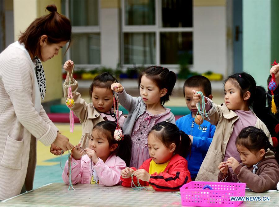 Children learn to knit a net for painted eggs under the guide of a teacher marking the upcoming \