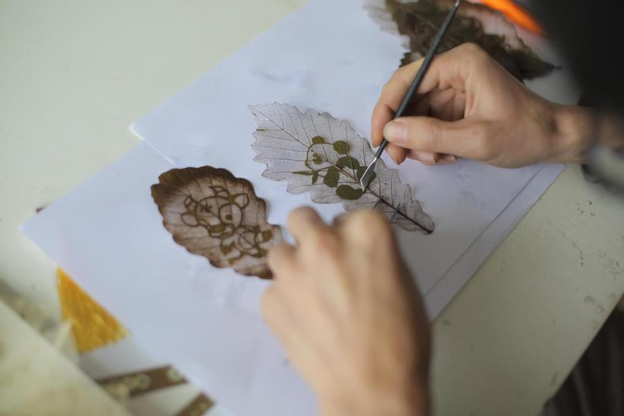 Deng Weiwei from Southwest China\'s Chongqing works on a leaf carving. At the recent International Handicrafts Trade Fair in Florence, Italy, Deng\'s work attracted considerable attention. (Photo provided to chinadaily.com.cn)