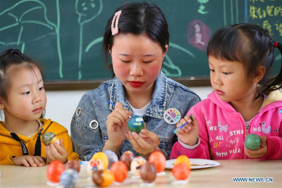 Children paint on eggs under the guide of a teacher to mark the upcoming \