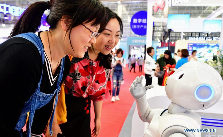 Two visitors interact with a robot at the 2nd Digital China Exhibition in Fuzhou, southeast China\'s Fujian Province, May 5, 2019. The 2nd Digital China Exhibition runs from May 5 to 9 at the Fuzhou Strait International Conference & Exhibition Center. (Xinhua/Wei Peiquan)