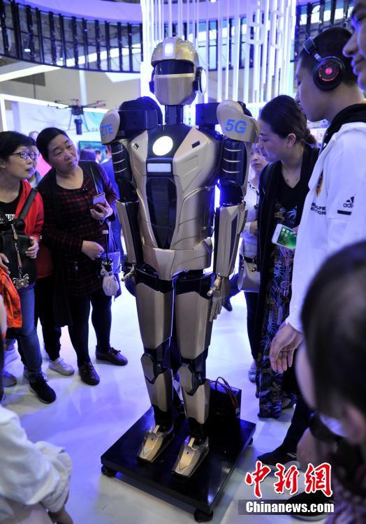 Visitors look at a 5G-powered robot at the ZTE booth during the second Digital China Summit in Fuzhou, East China\'s Fujian Province, May 6, 2019. (Photo: China News Service/Zhang Bin)
