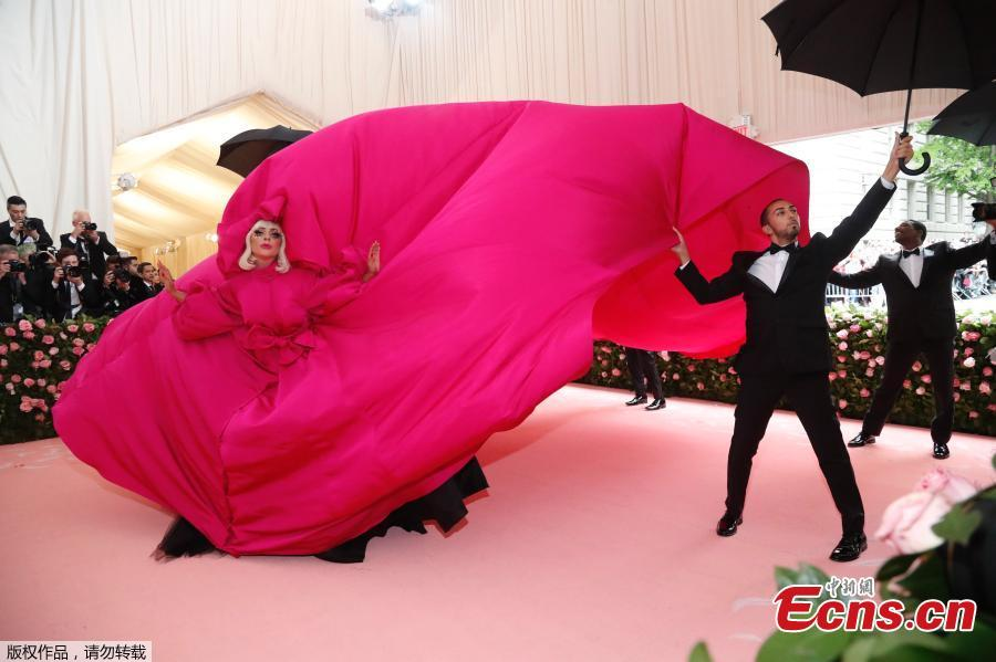 """Lady Gaga arrives in a fuchsia dress with an enormous train and an entourage of umbrella-holding, suit-wearing men to handle it at the Metropolitan Museum of Art on May 6, 2019, in New York.  (Photo/Agencies)  The red carpet was rolled out and celebrities made grand entrances with outfits based on their interpretation of the theme, """"Camp: Notes on Fashion"""", at the 2019 Met Gala in New York City on Monday."""