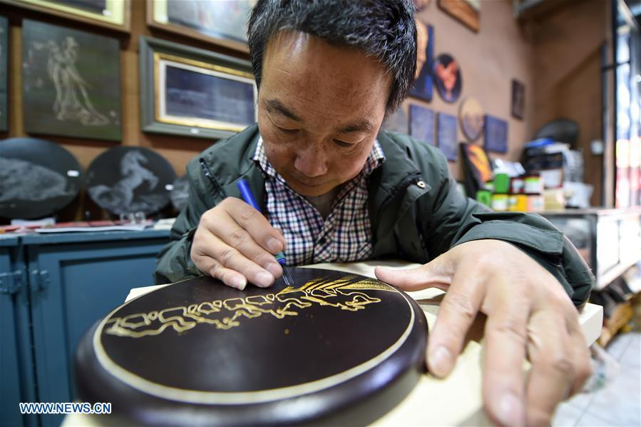 Shen Hongjie makes a woodcut at his workshop in Dunhuang, northwest China\'s Gansu Province, May 6, 2019. In 2004, Shen Hongjie was impressed by Dunhuang culture as he came here for sightseeing. He then left his hometown in central China\'s Hunan Province for Dunhuang. For 15 years, Shen Hongjie has been dedicated to promoting Dunhuang culture through woodcut. (Xinhua/Fan Peishen)