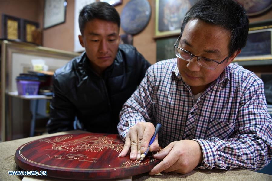Shen Hongjie (R) teaches his apprentice at his workshop in Dunhuang, northwest China\'s Gansu Province, May 6, 2019. In 2004, Shen Hongjie was impressed by Dunhuang culture as he came here for sightseeing. He then left his hometown in central China\'s Hunan Province for Dunhuang. For 15 years, Shen Hongjie has been dedicated to promoting Dunhuang culture through woodcut. (Xinhua/Fan Peishen)