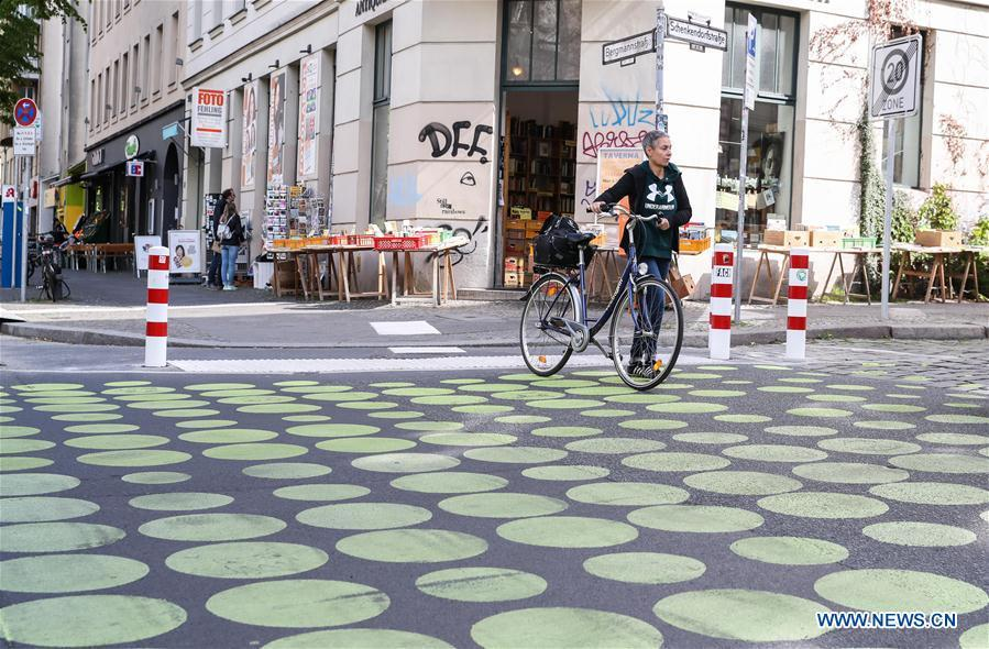 A pedestrian with a bicycle walks across a green dotted street area in Bergmann Street of Kreuzberg, southern Berlin, Germany, on May 7, 2019. The green dots, part of new street signals in Berlin, are applied as a trial at a part of Bergmann Street with a speed limit of 20km/h, aiming to induce vehicles to drive with restricted speed. (Xinhua/Shan Yuqi)