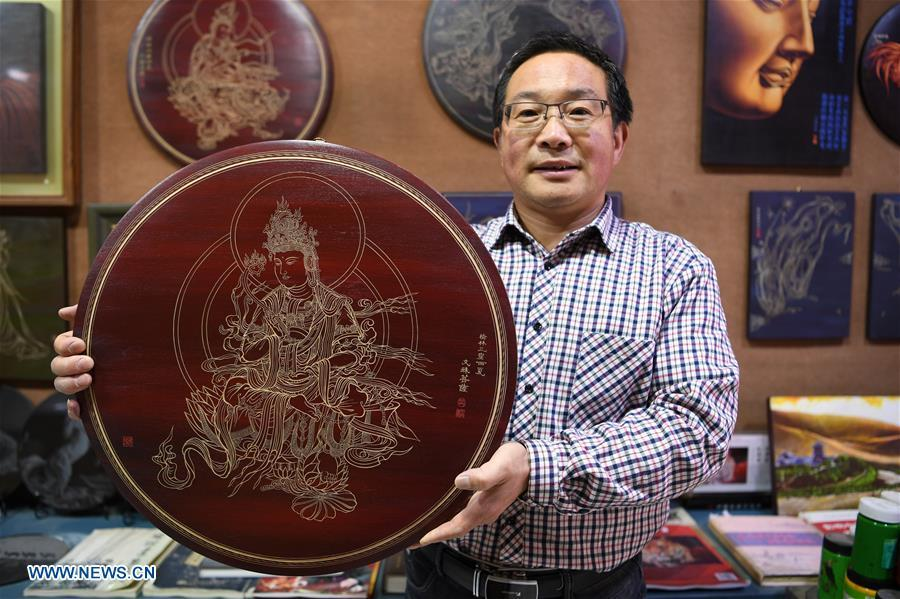 Shen Hongjie shows his woodcut work at his workshop in Dunhuang, northwest China\'s Gansu Province, May 6, 2019. In 2004, Shen Hongjie was impressed by Dunhuang culture as he came here for sightseeing. He then left his hometown in central China\'s Hunan Province for Dunhuang. For 15 years, Shen Hongjie has been dedicated to promoting Dunhuang culture through woodcut. (Xinhua/Fan Peishen)