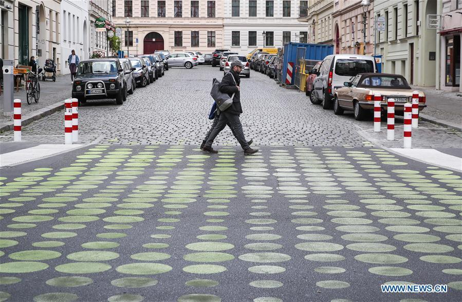 Two pedestrians walk across a green dotted street area in Bergmann Street of Kreuzberg, southern Berlin, Germany, on May 7, 2019. The green dots, part of new street signals in Berlin, are applied as a trial at a part of Bergmann Street with a speed limit of 20km/h, aiming to induce vehicles to drive with restricted speed. (Xinhua/Shan Yuqi)