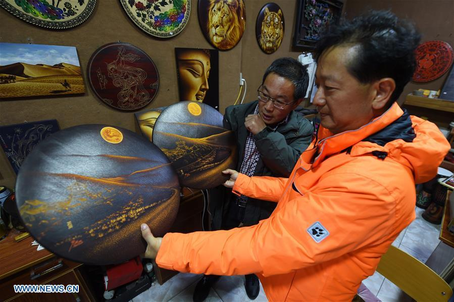Shen Hongjie (L) introduces his woodcut work at his workshop in Dunhuang, northwest China\'s Gansu Province, May 6, 2019. In 2004, Shen Hongjie was impressed by Dunhuang culture as he came here for sightseeing. He then left his hometown in central China\'s Hunan Province for Dunhuang. For 15 years, Shen Hongjie has been dedicated to promoting Dunhuang culture through woodcut. (Xinhua/Fan Peishen)