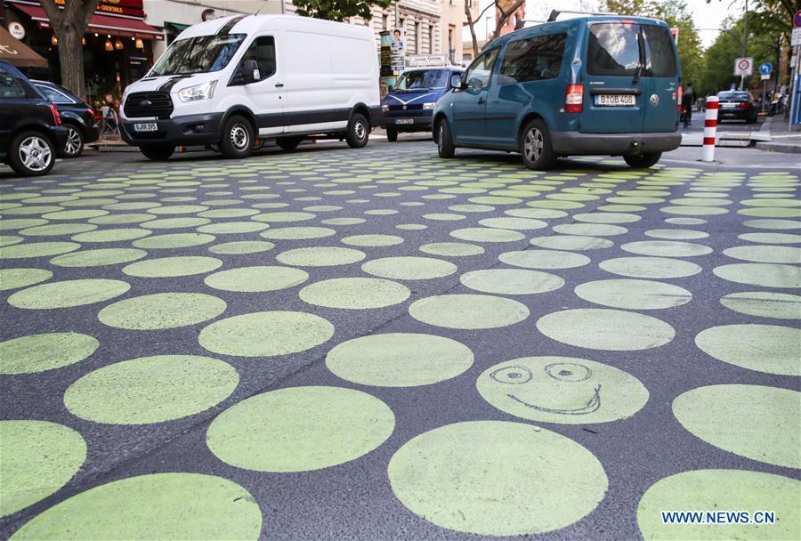 Vehicles drive across a green dotted street area in Bergmann Street of Kreuzberg, southern Berlin, Germany, on May 7, 2019. The green dots, part of new street signals in Berlin, are applied as a trial at a part of Bergmann Street with a speed limit of 20km/h, aiming to induce vehicles to drive with restricted speed. (Xinhua/Shan Yuqi)