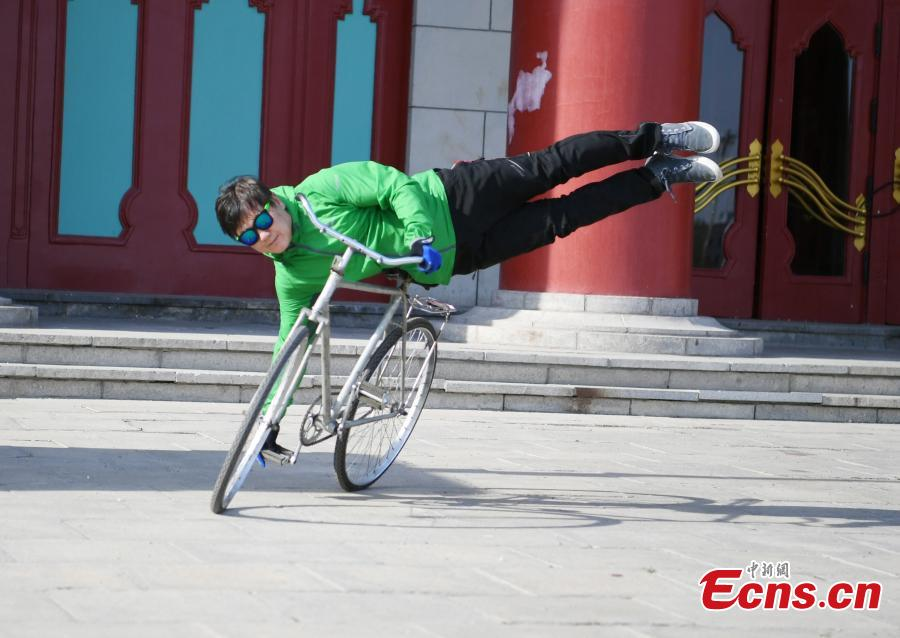 Zhou Changchun, 59, shows off his cycling stunts at a square in Changchun City, Northeast China\'s Jilin Province, May 7, 2019. Zhou is able to perform a number of stunts while riding his bicycle, including standing and lifting dumbbells with both hands. (Photo: China News Service/Zhang Yao)