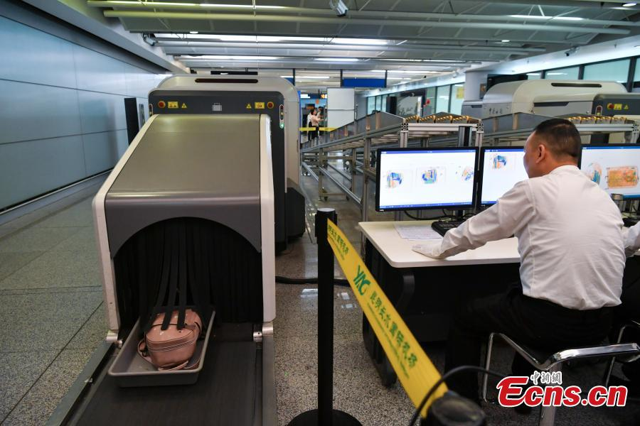 A Kunming Customs officer checks a passenger\'s luggage using a scanner at the Changshui International Airport in Kunming City, Yunnan Province, May 8, 2019. Kunming Customs showcased endangered species and wildlife products seized by staff at the airport. (Photo: China News Service/Ren Dong)