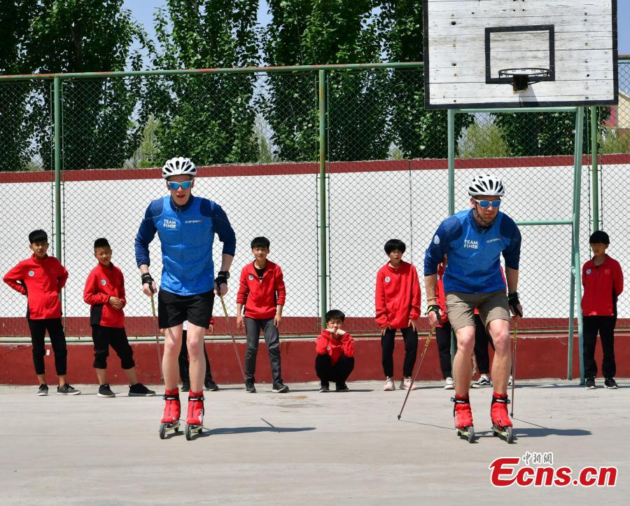 Coaches from Finland instruct students at the Youth Winter Olympic Sports School, or Xuanhua No. 2 Middle School, in Zhangjiakou, Hebei Province, May 9, 2019. The school established in 2015 is the only of its kind to specialize on training of Winter Olympic sports in China. The school has recruited more than 1,200 students, including 200 trained to be competitive skiers. Located some 200km northwest of Beijing, Zhangjiakou will host snowboarding, freestyle skiing, cross-country skiing, ski jumping, Nordic combined and biathlon competitions during the 2022 Winter Games. (Photo: China News Service/Zhai Yujia)