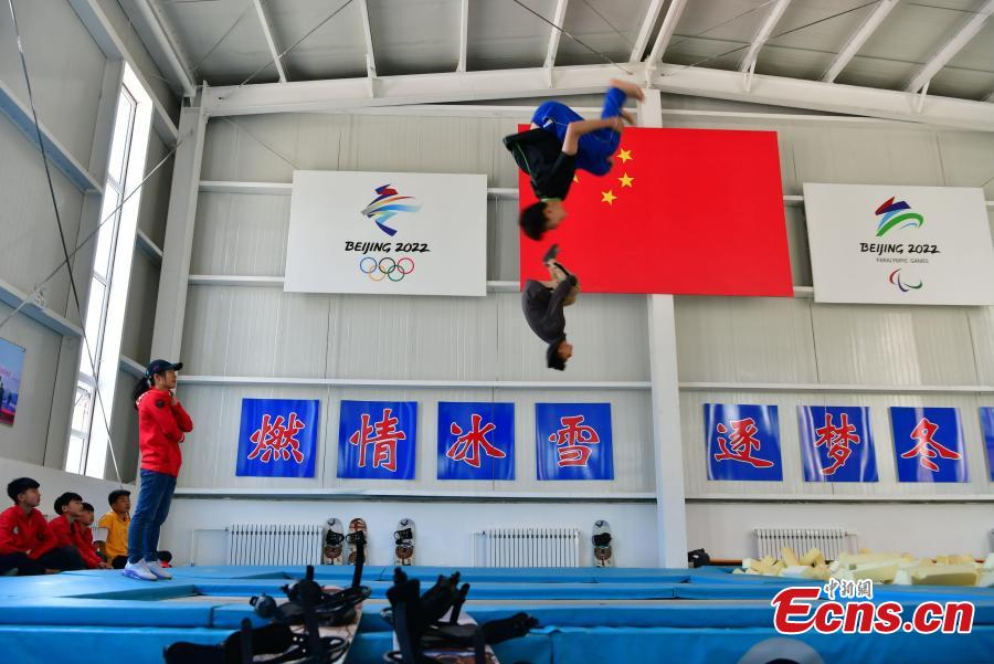A student practices snowboarding under the instruction of coach Sun Zhifeng (with blue hat) at the Youth Winter Olympic Sports School, or Xuanhua No. 2 Middle School, in Zhangjiakou, Hebei Province, May 9, 2019. The school established in 2015 is the only of its kind to specialize on training of Winter Olympic sports in China. The school has recruited more than 1,200 students, including 200 trained to be competitive skiers. Located some 200km northwest of Beijing, Zhangjiakou will host snowboarding, freestyle skiing, cross-country skiing, ski jumping, Nordic combined and biathlon competitions during the 2022 Winter Games. (Photo: China News Service/Zhai Yujia)