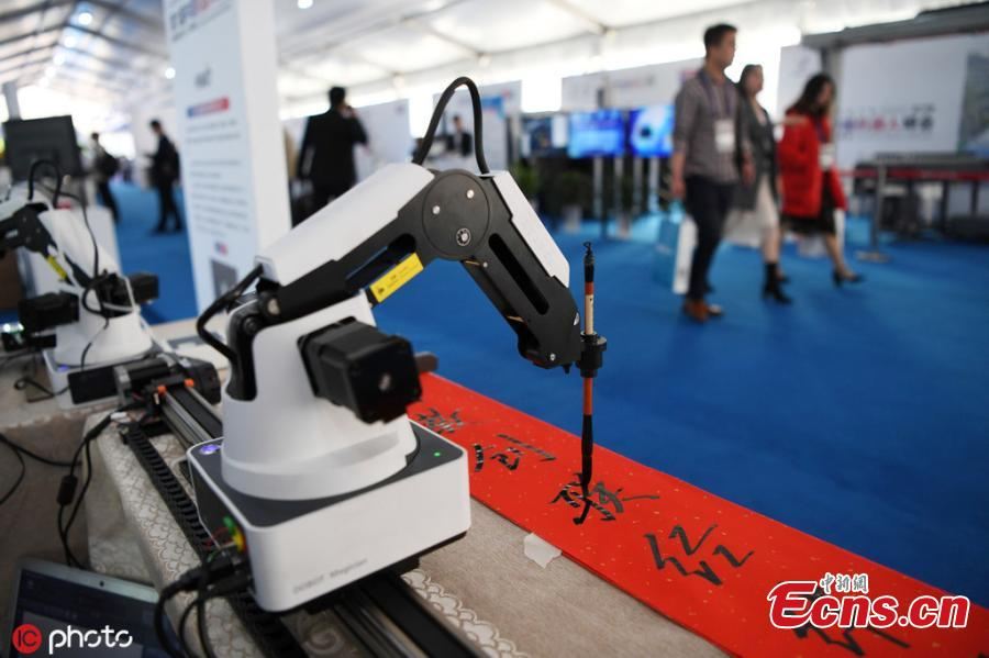 A robot performs tasks including writing calligraphy with a brush, cooking, and delivering beer after opening a bottle all on its own during the 6th China Robotop Summit in Ningbo City, East China\'s Zhejiang Province, May 9, 2019. According to its official website, the summit aims to promote the application of robots in intelligent manufacturing. (Photo/IC)