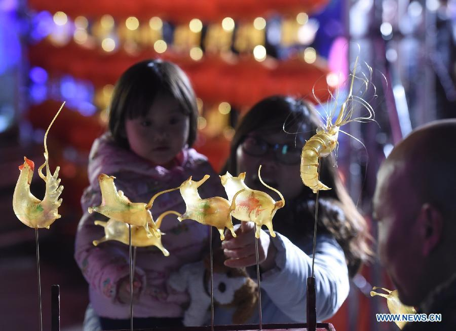 People view a performance of sugar-figure blowing by a folk artist during a lantern fair in Beijing, capital of China, Feb. 28, 2018. China will hold the Conference on Dialogue of Asian Civilizations starting from May 15. Under the theme of \
