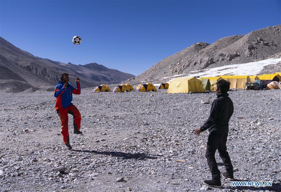 The mountain guide Zhaxi Dondrup plays football at the base camp of the northern face of Mount Qomolangma in southwest China\'s Tibet Autonomous Region, April 26, 2019. Every year, for a few weeks, hundreds of climbers and supporting personnel come to the base camp of the northern face of Mount Qomolangma, trying to reach the summit of the tallest and most famous mountain in the world. Before starting climbing, they need to hike several times between elevations from 5,000 meters to 7,000 meters, giving their bodies some time to adapt. When this process is over, it\'s all up to the weather. The base camp is a popular place to wait for the window. Among the six camps on the northern face, the base camp at an altitude of 5,200 meters is the furthest cars can reach and therefor the most equipped. Besides food and accommodation, climbers can also enjoy tea and massage. They can also play football on perhaps the highest field. There\'s even a simple gym in the camp. Environmental protection is a priority here. Garbage sacks are given to each climbing team. Special containers are put in every camp to collect trash and sewage. The collected trash must be treated 100 kilometers away, and the only road is a zigzagging track. It is not trucks, but yaks that are generally used to make the journey. Actually yaks are vital on the mountain. Beyond the base camp, yak is the only reliable transport. (Xinhua/Sun Fei)