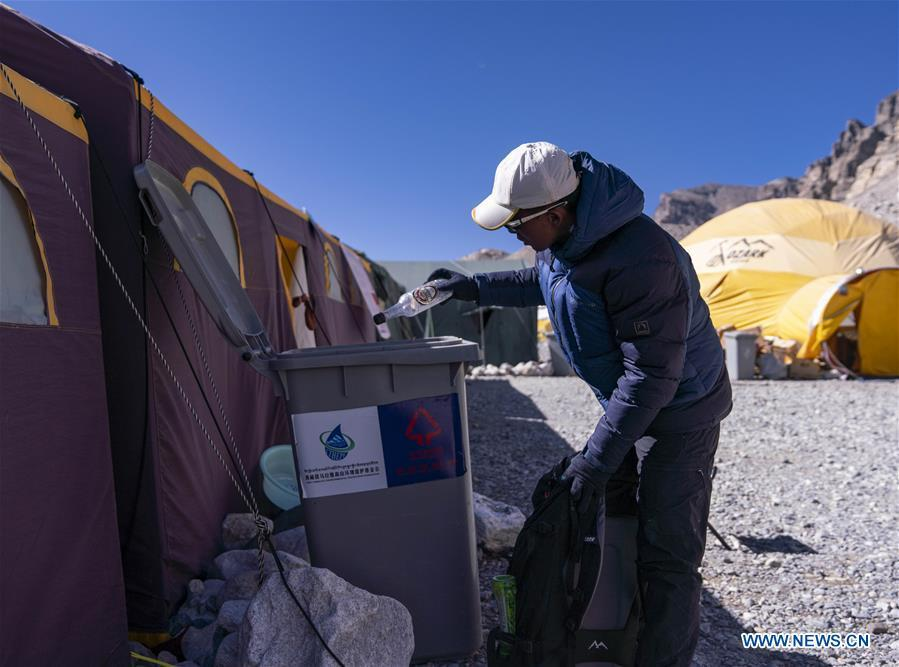 The mountain guide Sonam Tsering throws the garbage into the trash can at the base camp of the northern face of Mount Qomolangma in southwest China\'s Tibet Autonomous Region, April 26, 2019. Every year, for a few weeks, hundreds of climbers and supporting personnel come to the base camp of the northern face of Mount Qomolangma, trying to reach the summit of the tallest and most famous mountain in the world. Before starting climbing, they need to hike several times between elevations from 5,000 meters to 7,000 meters, giving their bodies some time to adapt. When this process is over, it\'s all up to the weather. The base camp is a popular place to wait for the window. Among the six camps on the northern face, the base camp at an altitude of 5,200 meters is the furthest cars can reach and therefor the most equipped. Besides food and accommodation, climbers can also enjoy tea and massage. They can also play football on perhaps the highest field. There\'s even a simple gym in the camp. Environmental protection is a priority here. Garbage sacks are given to each climbing team. Special containers are put in every camp to collect trash and sewage. The collected trash must be treated 100 kilometers away, and the only road is a zigzagging track. It is not trucks, but yaks that are generally used to make the journey. Actually yaks are vital on the mountain. Beyond the base camp, yak is the only reliable transport. (Xinhua/Sun Fei)