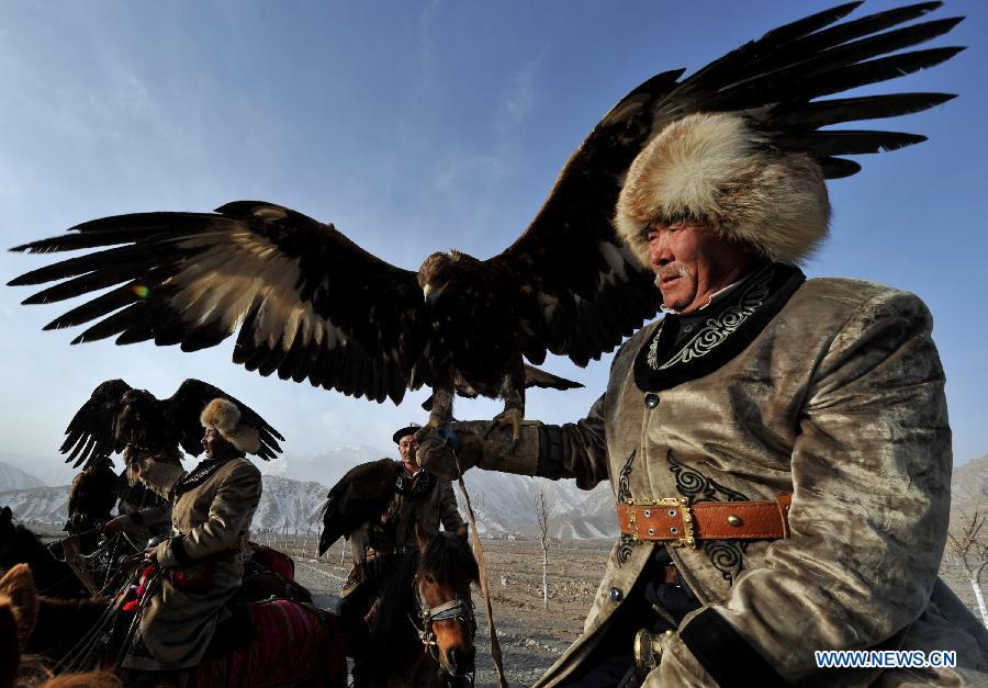 Herdsmen of Kirgiz ethnic group ride with their falcons in Akqi County, northwest China\'s Xinjiang Uygur Autonomous Region, March 20, 2011. China will hold the Conference on Dialogue of Asian Civilizations starting from May 15. Under the theme of \