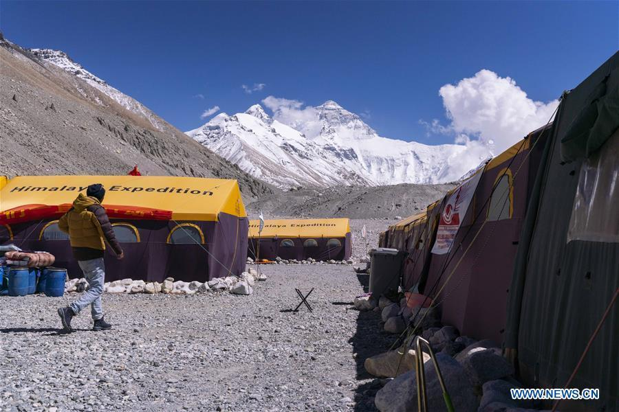 The Chinese mountaineering camp is seen at the base camp of the northern face of Mount Qomolangma in southwest China\'s Tibet Autonomous Region, April 26, 2019. Every year, for a few weeks, hundreds of climbers and supporting personnel come to the base camp of the northern face of Mount Qomolangma, trying to reach the summit of the tallest and most famous mountain in the world. Before starting climbing, they need to hike several times between elevations from 5,000 meters to 7,000 meters, giving their bodies some time to adapt. When this process is over, it\'s all up to the weather. The base camp is a popular place to wait for the window. Among the six camps on the northern face, the base camp at an altitude of 5,200 meters is the furthest cars can reach and therefor the most equipped. Besides food and accommodation, climbers can also enjoy tea and massage. They can also play football on perhaps the highest field. There\'s even a simple gym in the camp. Environmental protection is a priority here. Garbage sacks are given to each climbing team. Special containers are put in every camp to collect trash and sewage. The collected trash must be treated 100 kilometers away, and the only road is a zigzagging track. It is not trucks, but yaks that are generally used to make the journey. Actually yaks are vital on the mountain. Beyond the base camp, yak is the only reliable transport. (Xinhua/Sun Fei)