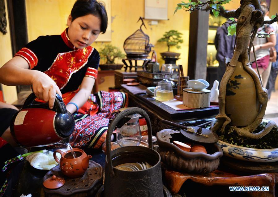 A tea artist performs tea art in Hanoi\'s Old Quarter, Vietnam, on Nov. 25, 2018. As an important part of Asian culture, tea is a special bond among Asian countries to deepen friendship and boost mutual exchanges. China will hold the Conference on Dialogue of Asian Civilizations starting from May 15. Under the theme of \