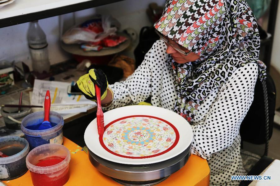An artist paints on a Cini base at a factory in Kutahay, Turkey, April 25, 2017. Cini is a kind of traditional faience pottery making industry originated in China. China will hold the Conference on Dialogue of Asian Civilizations starting from May 15. Under the theme of \
