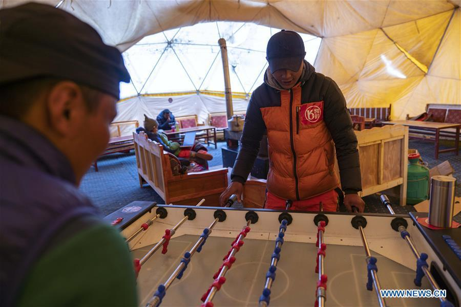 Climbers play table football in the tent of the Chinese mountaineering team at the base camp of the northern face of Mount Qomolangma in southwest China\'s Tibet Autonomous Region, April 25, 2019. Every year, for a few weeks, hundreds of climbers and supporting personnel come to the base camp of the northern face of Mount Qomolangma, trying to reach the summit of the tallest and most famous mountain in the world. Before starting climbing, they need to hike several times between elevations from 5,000 meters to 7,000 meters, giving their bodies some time to adapt. When this process is over, it\'s all up to the weather. The base camp is a popular place to wait for the window. Among the six camps on the northern face, the base camp at an altitude of 5,200 meters is the furthest cars can reach and therefor the most equipped. Besides food and accommodation, climbers can also enjoy tea and massage. They can also play football on perhaps the highest field. There\'s even a simple gym in the camp. Environmental protection is a priority here. Garbage sacks are given to each climbing team. Special containers are put in every camp to collect trash and sewage. The collected trash must be treated 100 kilometers away, and the only road is a zigzagging track. It is not trucks, but yaks that are generally used to make the journey. Actually yaks are vital on the mountain. Beyond the base camp, yak is the only reliable transport. (Xinhua/Sun Fei)