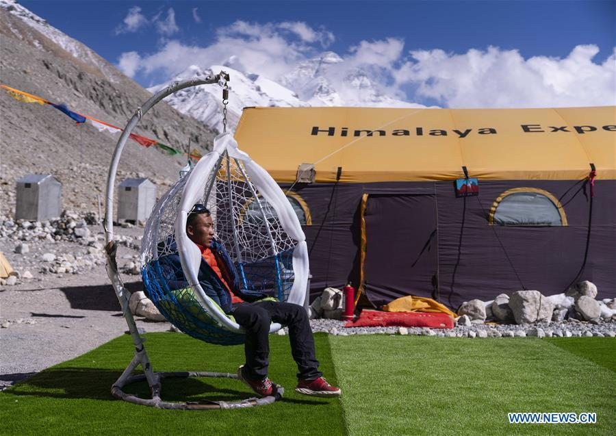 The mountain guide Sonam Tsering takes a break at the base camp of the northern face of Mount Qomolangma in southwest China\'s Tibet Autonomous Region, April 26, 2019. Every year, for a few weeks, hundreds of climbers and supporting personnel come to the base camp of the northern face of Mount Qomolangma, trying to reach the summit of the tallest and most famous mountain in the world. Before starting climbing, they need to hike several times between elevations from 5,000 meters to 7,000 meters, giving their bodies some time to adapt. When this process is over, it\'s all up to the weather. The base camp is a popular place to wait for the window. Among the six camps on the northern face, the base camp at an altitude of 5,200 meters is the furthest cars can reach and therefor the most equipped. Besides food and accommodation, climbers can also enjoy tea and massage. They can also play football on perhaps the highest field. There\'s even a simple gym in the camp. Environmental protection is a priority here. Garbage sacks are given to each climbing team. Special containers are put in every camp to collect trash and sewage. The collected trash must be treated 100 kilometers away, and the only road is a zigzagging track. It is not trucks, but yaks that are generally used to make the journey. Actually yaks are vital on the mountain. Beyond the base camp, yak is the only reliable transport. (Xinhua/Sun Fei)