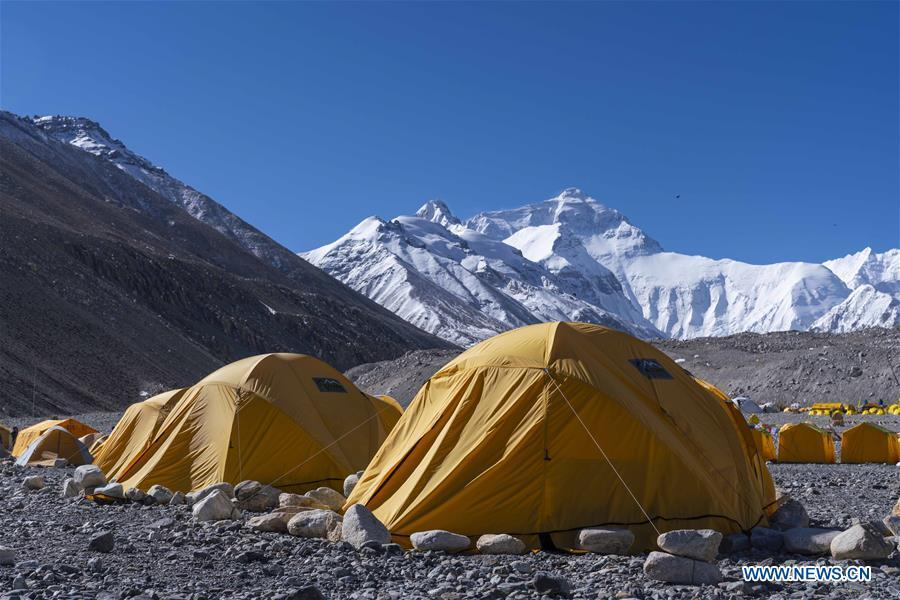 Tents of expedition teams are seen at the base camp of the northern face of Mount Qomolangma in southwest China\'s Tibet Autonomous Region, April 25, 2019. Every year, for a few weeks, hundreds of climbers and supporting personnel come to the base camp of the northern face of Mount Qomolangma, trying to reach the summit of the tallest and most famous mountain in the world. Before starting climbing, they need to hike several times between elevations from 5,000 meters to 7,000 meters, giving their bodies some time to adapt. When this process is over, it\'s all up to the weather. The base camp is a popular place to wait for the window. Among the six camps on the northern face, the base camp at an altitude of 5,200 meters is the furthest cars can reach and therefor the most equipped. Besides food and accommodation, climbers can also enjoy tea and massage. They can also play football on perhaps the highest field. There\'s even a simple gym in the camp. Environmental protection is a priority here. Garbage sacks are given to each climbing team. Special containers are put in every camp to collect trash and sewage. The collected trash must be treated 100 kilometers away, and the only road is a zigzagging track. It is not trucks, but yaks that are generally used to make the journey. Actually yaks are vital on the mountain. Beyond the base camp, yak is the only reliable transport. (Xinhua/Sun Fei)