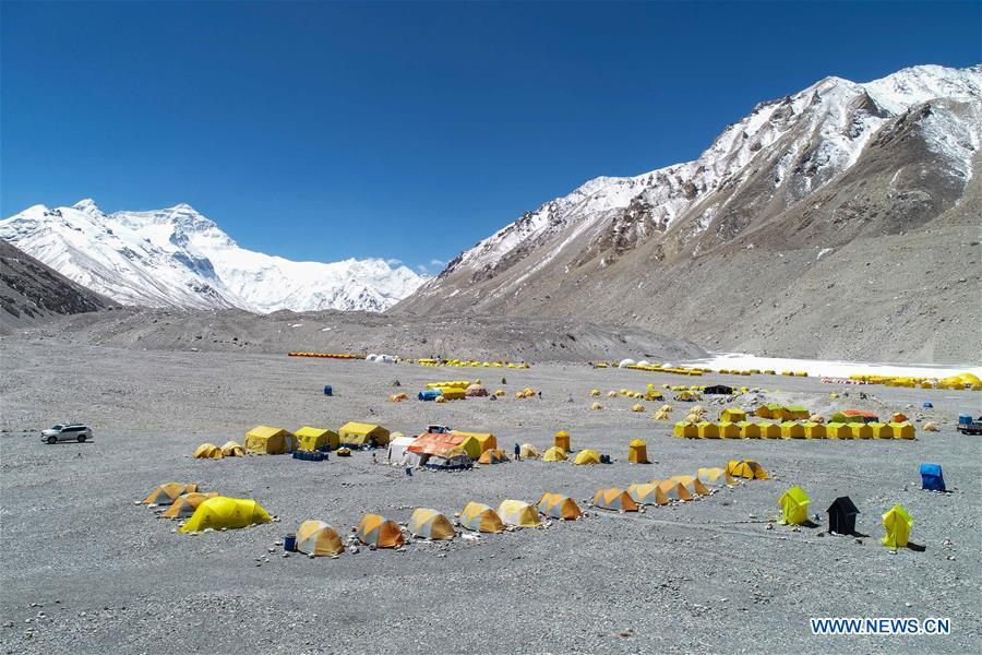 Aerial photo taken on April 25, 2019 shows the base camp of the northern face of Mount Qomolangma in southwest China\'s Tibet Autonomous Region. Every year, for a few weeks, hundreds of climbers and supporting personnel come to the base camp of the northern face of Mount Qomolangma, trying to reach the summit of the tallest and most famous mountain in the world. Before starting climbing, they need to hike several times between elevations from 5,000 meters to 7,000 meters, giving their bodies some time to adapt. When this process is over, it\'s all up to the weather. The base camp is a popular place to wait for the window. Among the six camps on the northern face, the base camp at an altitude of 5,200 meters is the furthest cars can reach and therefor the most equipped. Besides food and accommodation, climbers can also enjoy tea and massage. They can also play football on perhaps the highest field. There\'s even a simple gym in the camp. Environmental protection is a priority here. Garbage sacks are given to each climbing team. Special containers are put in every camp to collect trash and sewage. The collected trash must be treated 100 kilometers away, and the only road is a zigzagging track. It is not trucks, but yaks that are generally used to make the journey. Actually yaks are vital on the mountain. Beyond the base camp, yak is the only reliable transport. (Xinhua/Sun Fei)