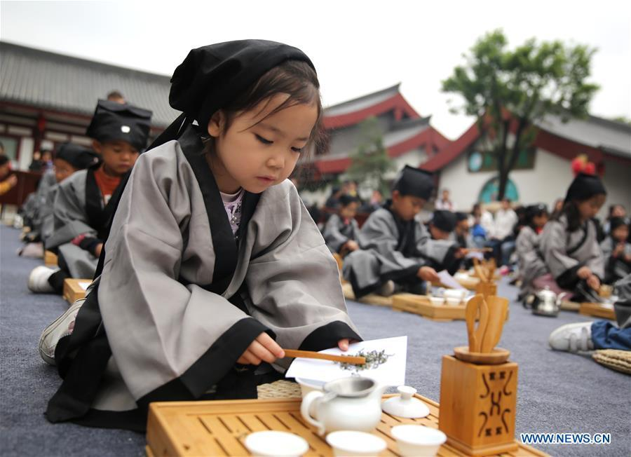 Children experience tea art in Jia Pingwa Pavillion in Xi\'an, northwest China\'s Shaanxi Province, on April 21, 2019. As an important part of Asian culture, tea is a special bond among Asian countries to deepen friendship and boost mutual exchanges. China will hold the Conference on Dialogue of Asian Civilizations starting from May 15. Under the theme of \