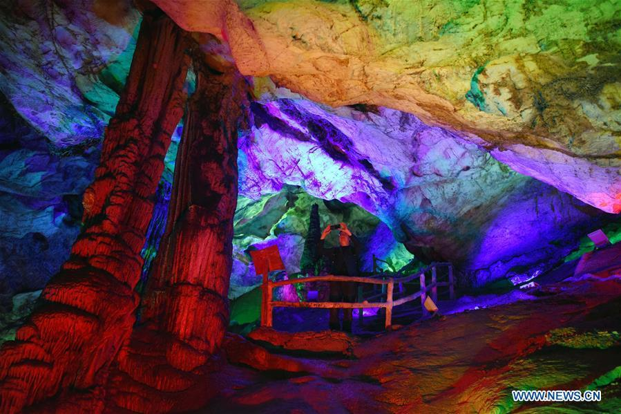 A tourist takes pictures in Wanxiang karst cave in Hanwang Township of Longnan City, northwest China\'s Gansu Province, May 13, 2019. (Xinhua/Ma Ning)