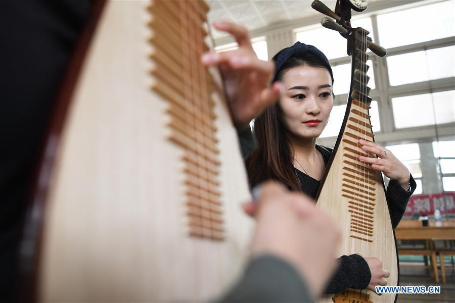 Player Zhao Xiaotong practices playing the pipa at Lanzhou traditional orchestra in Lanzhou, northwest China\'s Gansu Province, May 13, 2019. Pipa, a pear-shaped stringed instrument, is one of the traditional Chinese musical instruments. The pipa is played vertically and can be found in solos, ensembles or orchestras. The images of flying apsaras playing the pipa have been seen on murals in Gansu\'s Dunhuang Mogao Grottoes, a 1,600-year-old UNESCO world heritage site located at a cultural and religious crossroads area on the ancient Silk Road in Gansu. Nowadays contemporary dance performances inspired from those images on the murals have been staged times and times again. (Xinhua/Chen Bin)