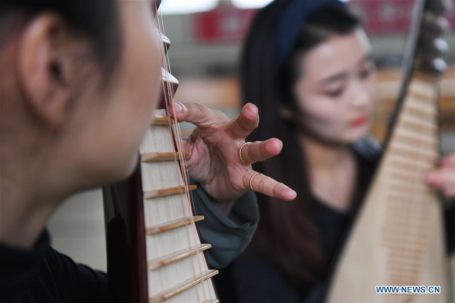 Players Zhang Geping (L) and Zhao Xiaotong practice playing the pipa at Lanzhou traditional orchestra in Lanzhou, northwest China\'s Gansu Province, May 13, 2019. Pipa, a pear-shaped stringed instrument, is one of the traditional Chinese musical instruments. The pipa is played vertically and can be found in solos, ensembles or orchestras. The images of flying apsaras playing the pipa have been seen on murals in Gansu\'s Dunhuang Mogao Grottoes, a 1,600-year-old UNESCO world heritage site located at a cultural and religious crossroads area on the ancient Silk Road in Gansu. Nowadays contemporary dance performances inspired from those images on the murals have been staged times and times again. (Xinhua/Chen Bin)
