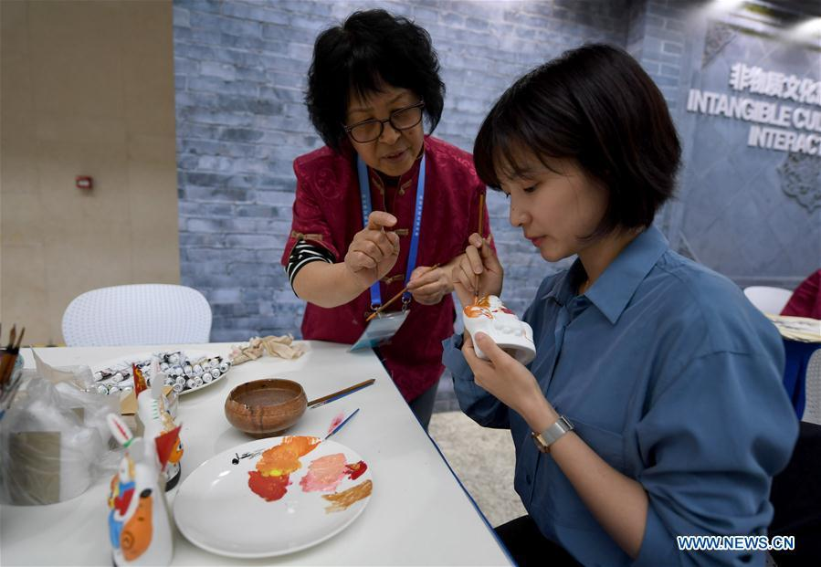 A reporter paints a clay sculpture at the intangible cultural heritage interactive area of the media center of the Conference on Dialogue of Asian Civilizations in the China National Convention Center in Beijing, capital of China, May 14, 2019. The Conference on Dialogue of Asian Civilizations will open on Wednesday. (Xinhua/Wang Yuguo)