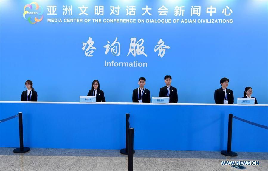 Volunteers work at the information desk of the media center of the Conference on Dialogue of Asian Civilizations in the China National Convention Center in Beijing, capital of China, May 14, 2019. The Conference on Dialogue of Asian Civilizations will open on Wednesday. (Xinhua/Wang Yuguo)