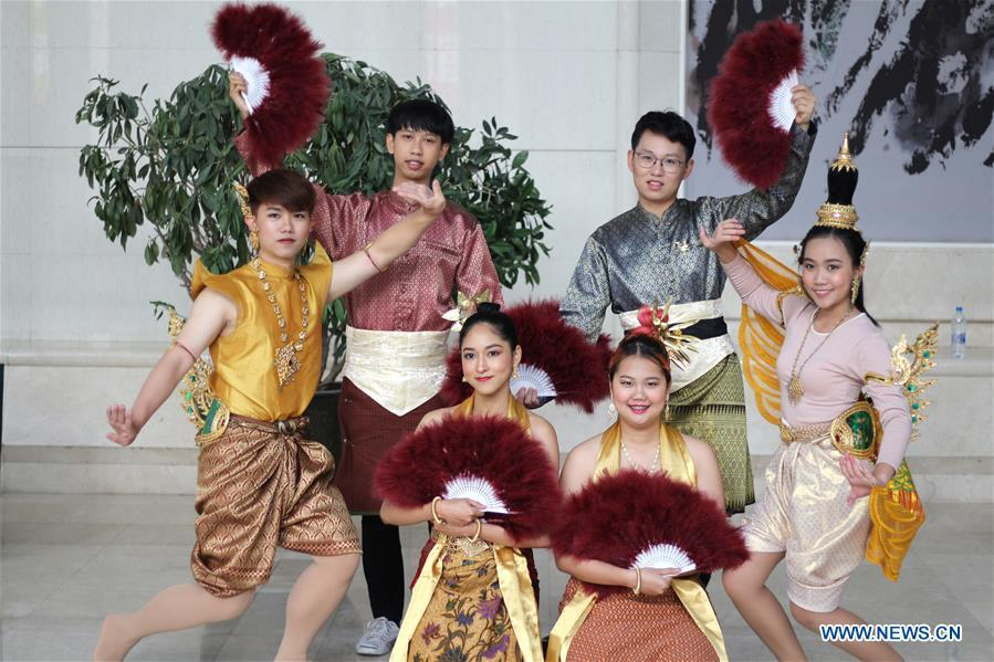 Ratjirot Aekkawat (R back) practices the Thai dance with other Thai students at the Peking University in Beijing, capital of China, Oct. 21, 2018. Ratjirot Aekkawat is of mixed blood from China and Thailand. He came to study in China as a junior student and now he is a postgraduate student of the Peking University. He always talks about his experience in China with relatives and friends. He has witnessed the development of China in recent years, during which the environment and local governments\' working efficiencies have been greatly improved. Chinese and Thai cultures are influenced with each other. Many Thai people celebrate the Spring Festival every year and lots of Chinese go to Thailand for tourism. The photo of the historical site of Ayutthaya Dynasty taken by Ratjirot Aekkawat will be displayed in a photographic exhibition \