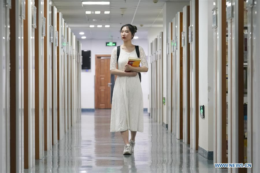 Feng Ganyu walks in a library at Beijing Normal University in Beijing, capital of China, May 12, 2019. A photographic exhibition themed \